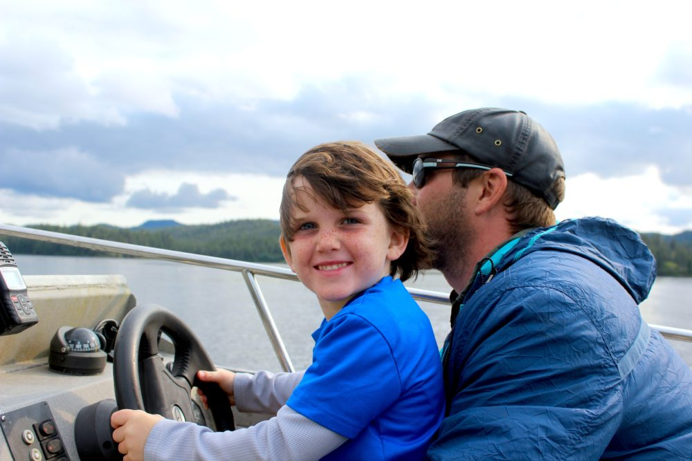 Father and son Ackerman at helm of skiff at The Lodge at Whale Pass